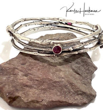 Load image into Gallery viewer, Apple branches are picked and cast in sterling silver, fabricated into a handmade bangle bracelet and four 6 mm rhodolite garnet gemstones are added. Bracelet is given an oxidized finish.