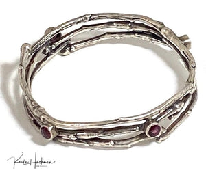 Apple branches are picked and cast in sterling silver, fabricated into a handmade bangle bracelet and four 6 mm rhodolite garnet gemstones are added. Bracelet is given an oxidized finish.