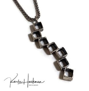 Seven vertical, stacked organic sterling silver open cubes, are combined in this pendant. Some cubes are hammered while others are left smooth. Texture is given an oxidized finish.