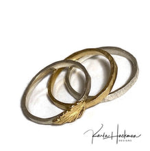 Load image into Gallery viewer, Set of three bands features:   1 solid 18 karat gold band with a hammered finish, 1 solid sterling silver band with a pebbled hammered finish, 1 solid sterling silver band topped with a solid 18 karat gold oak leaf
