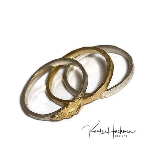 Set of three bands features:   1 solid 18 karat gold band with a hammered finish, 1 solid sterling silver band with a pebbled hammered finish, 1 solid sterling silver band topped with a solid 18 karat gold oak leaf