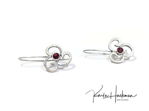 Sterling silver 3-petal flair design open form flower earrings have a light texture and a 5mm red garnet gemstone at their center.  Hand fabricated.