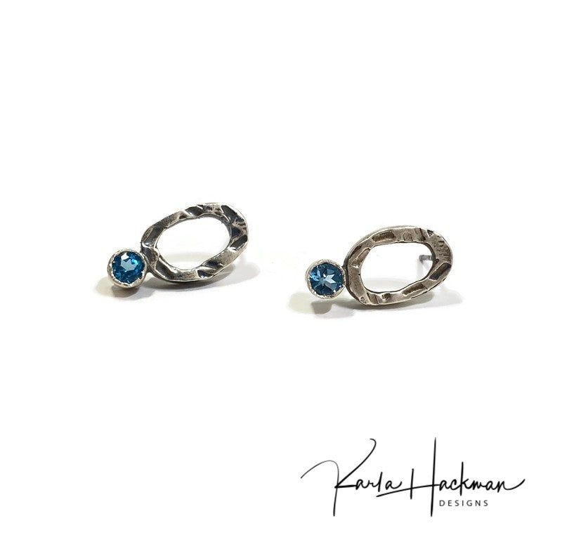 Freeform sterling silver oval studs are uniquely textured. Stud is adorned with a 4mm stone, blue or natural (clear) topaz, that sits just below the lobe. Earrings are lightly oxidized to highlight the design.