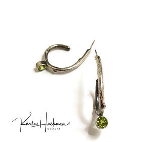 Sterling silver apple branches are picked from Karla's garden, cast and transformed into solid silver hoop earrings, and finished with hand fabrication. Branch texture is highlighted with oxidized patina, and a 5mm peridot gemstone adorns the bottom of each hoop.
