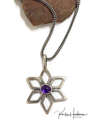 A six-pointed star flower pendant with marquis shaped petals is fabricated in sterling silver and given a hammered texture.   To accent the flower, a rich gemmy amethyst in a handmade bezel sits in the center of the pendant.  Pendant hangs from a fancy 18