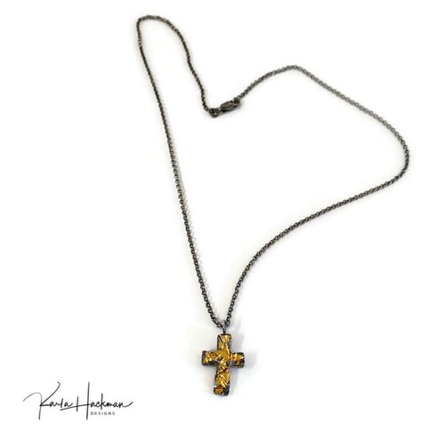 The cross, a Karla Hackman Designs original, was first hand-carved in wax and then cast in fine silver. Using Keum Boo, an ancient Korean gilding technique, thin layers of 24 solid gold were then fused to the cross.   Combining my love of wax carving with this ancient jewelry technique resulted in this beautiful one-of-a-kind piece of jewelry.  The piece is then finished with heavy oxidation to highlight the rich gold luster. The reverse side, is fine silver highlighted with oxidation.