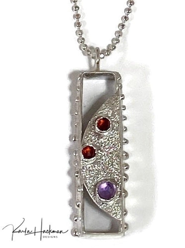 A hollow tapered rectangle is carved in wax and cast in sterling silver and is decorated on 3 sides.  Front facing panel has a hammered texture and 3 rose cut gemstones, two garnets and one amethyst.
