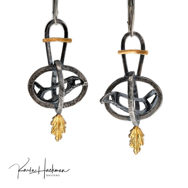 These hand-fabricated and unique caged bird earrings are sterling silver and 18 karat gold, and feature a bird outline sitting in an open cage. Silver is hammer textured and oxidized to highlight the contrast between the silver and gold.