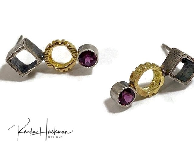 These stud earrings combine sterling silver cubes and 18 karat gold circles with 4mm gemstones, either rhodolite garnets or aquamarines. Cubes and circles are both textured inside and out, and silver is oxidized to highlight the rich gold.