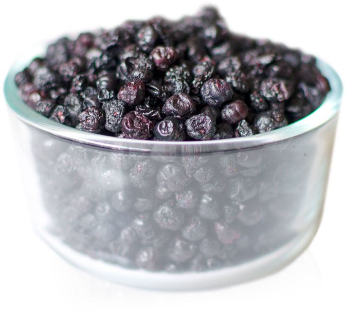 A glass bowl filled with dried crunchy wild blueberries.