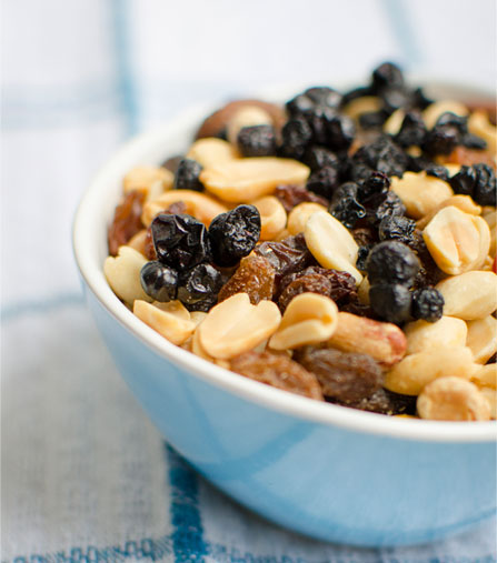 A bowl of assorted nuts and dried fruit, topped with chewy wild blueberries.