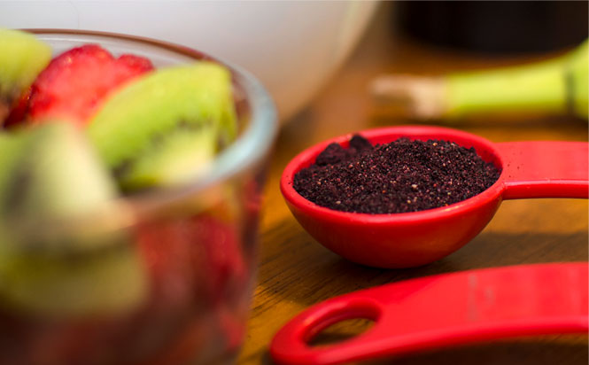 A bowl of assorted fruit next to a teaspoon measure filled with powdered wild blueberries.