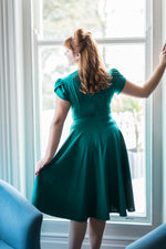 Woman in 1940s green dress looking out of a window