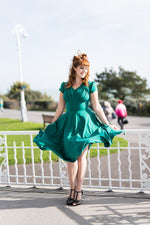 1940s swing dress in emerald green with skirt blowing in the wind