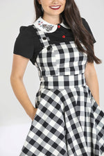 girl in gingham pinafore dress with hand in pocket