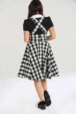 girl in gingham pinafore dress facing backwards