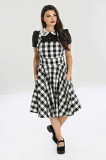 girl in gingham pinafore dress