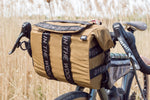 Load image into Gallery viewer, Dyed in the Wool XL bike handle bar bag, shown in brown X-pac attached to a adventure gravel bike. This large bag is a modern take on the classic Randonneur bags. DITW