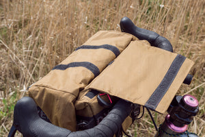 Dyed in the Wool XL bike handle bar bag, shown in brown X-pac attached to a adventure gravel bike. This large bag is a modern take on the classic Randonneur bags. DITW