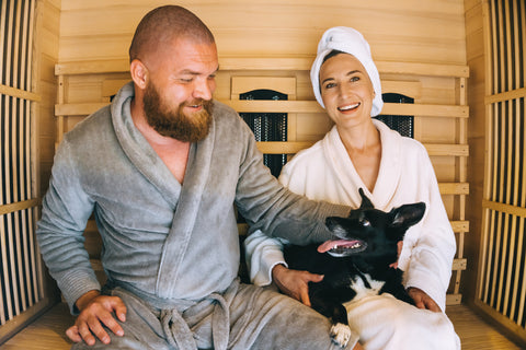 Happy smiling couple sitting inside an infrared sauna with little dog. Home spa, family relax day concept