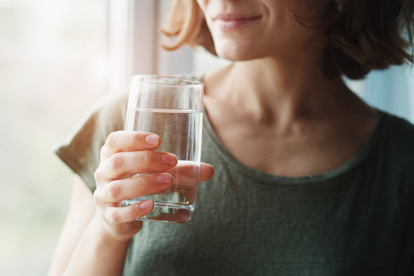 spring water glass held by woman in green Tshirt