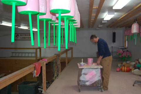 Josh Miller touches up his signature pink buoys during the winter.