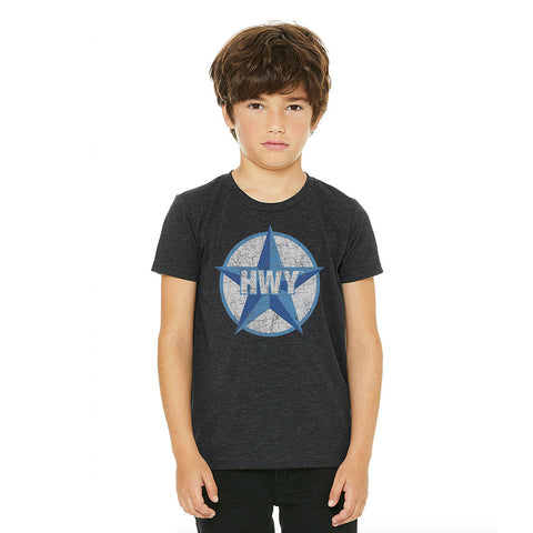 A kid wearing a Charcoal T-Shirt with a two toned blue graphic of the Blue Star Highway logo on it.