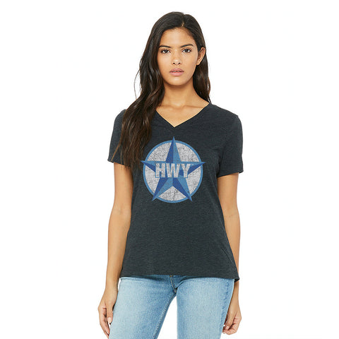A woman wearing a Charcoal V Neck Relaxed fit T-Shirt with a two toned blue graphic of the Blue Star Highway logo on it.