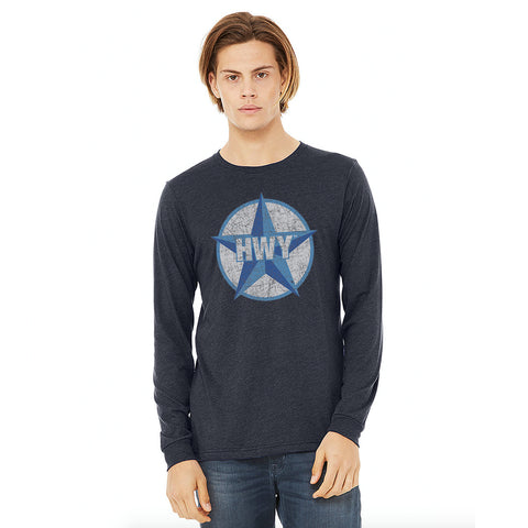 A guy wearing a Vintage Heather Navy Long Sleeve T-Shirt with a two toned blue graphic of the Blue Star Highway logo on it.