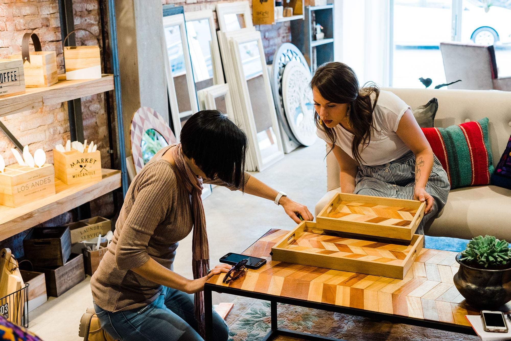 Kelsie and Eugenia consulting on wood mosaic design over wood mosaic trays and coffee table.