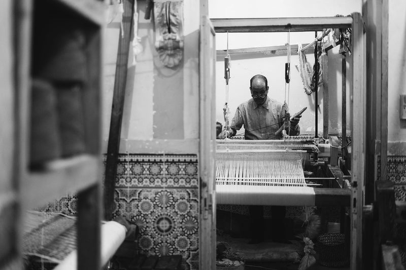 A weaver stands at a large loom in a workshop with Moroccan style tiled walls and other looms
