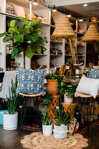 Photo shows Driftless Style's brick and mortar shop entry filled with plants in artisan-made pots, artisan made furniture, pillows, lampshade, and many other handmade products.
