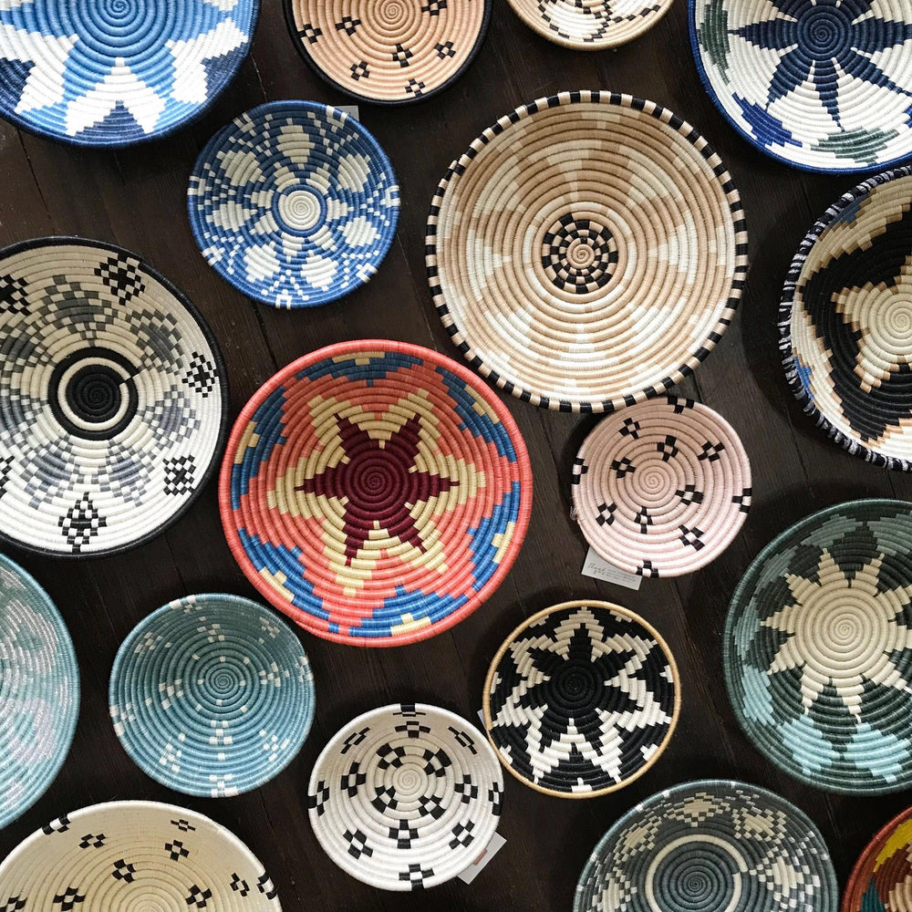 A bold and brightly colored grouping of handmade Rwandan coiled baskets.