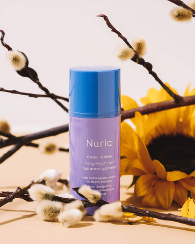 Nuria Calm Daily Moisturizer - bottle sitting with cottongrass and daisies