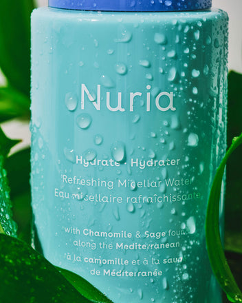 Nuria Hydrate Refreshing Micellar Water - bottle with droplets resting amongst green leaves