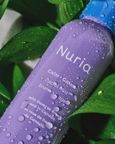 Nuria Calm Facial Mist -- bottle with water droplets laying in green leaves