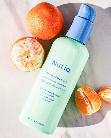 Nuria Rescue Rebalancing Cleanser - bottle on marble counter with ingredient, mandarin oranges, surrounding