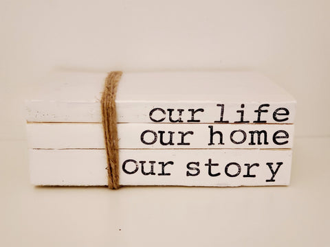 """our life, our home, our story"" book stack"