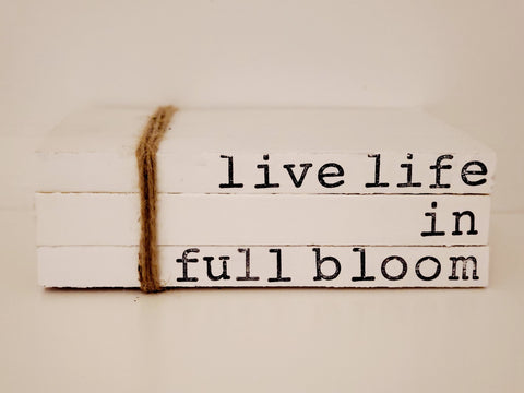 """live life in full bloom"" book stack"