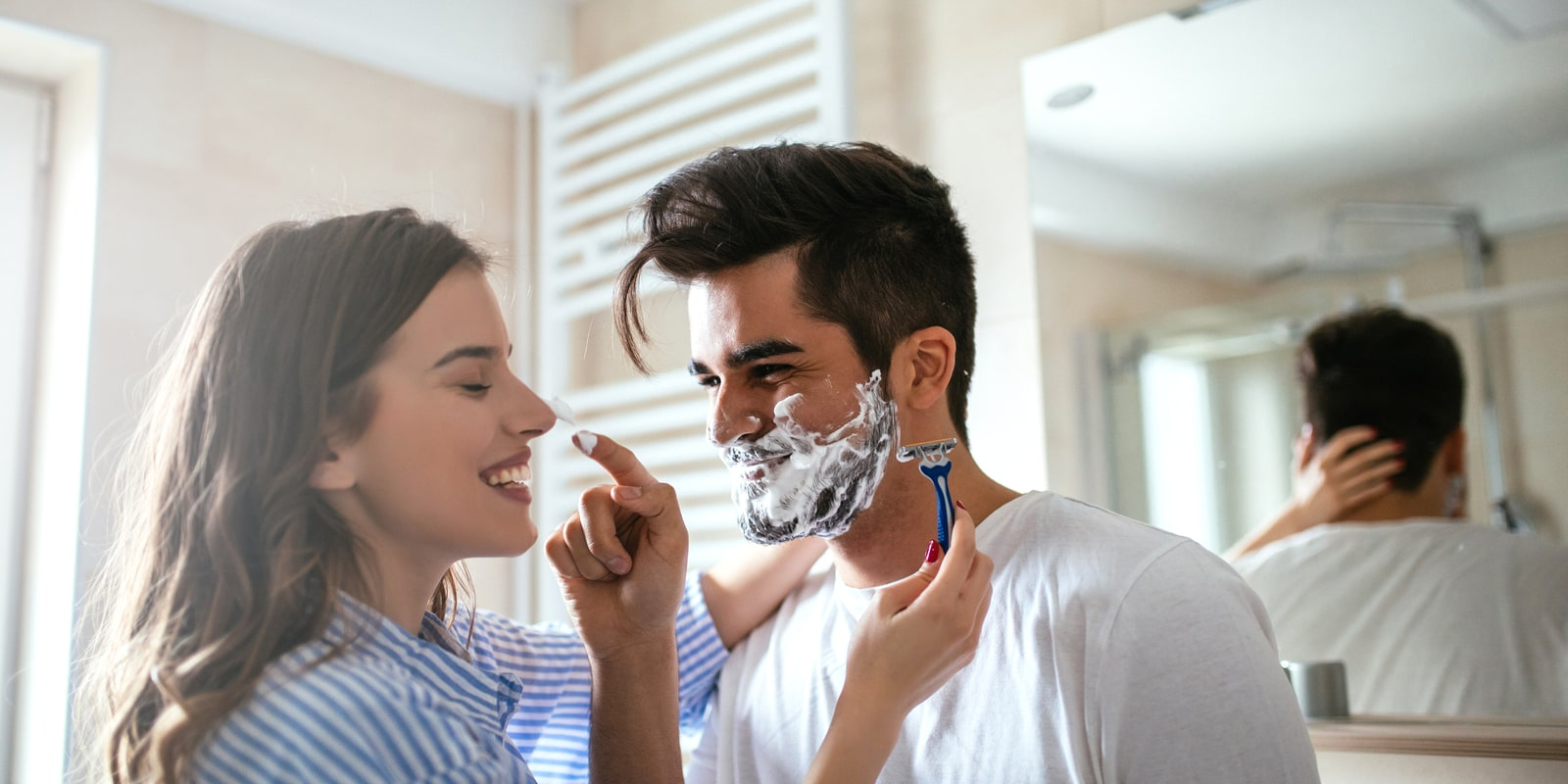 Woman helping man shave his face