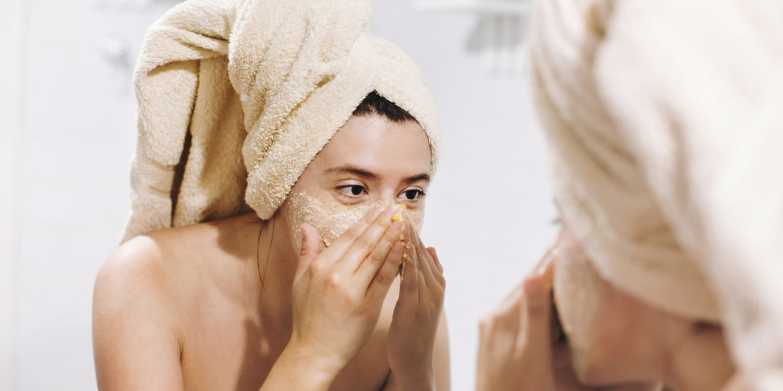 Woman cleansing and washing her face