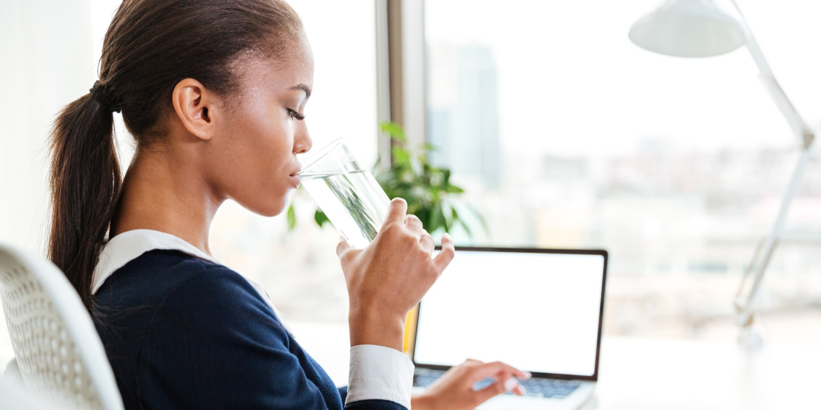 Woman drinking water sitting at her computer