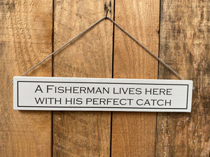 "Sign - ""A fisherman lives here with his perfect catch"""