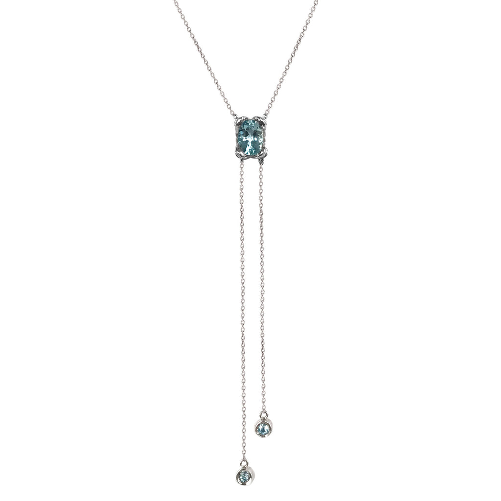 A beautiful lariat necklace with a large aquamarine in a K8 Jewelry exclusive petal setting. Two strands of chain finished with double-set precious stones dangle from the center stone.