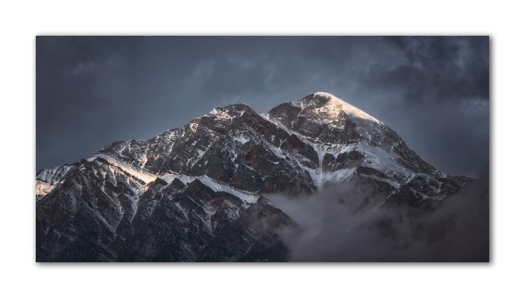 The sun gently kisses the top of this mountain peak in  Jasper Alberta Canada. The snow capped mountain top is warmed from the sun rays - Ready to hang on your wall