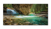 Load image into Gallery viewer, Once a hidden Gem in Johnston Canyon in the Banff National Park is now closed to foot traffic for environmental reasons. This amazing photo showcases the rock formations in the mountains and powerful waterfalls that carry the aqua water through the forest