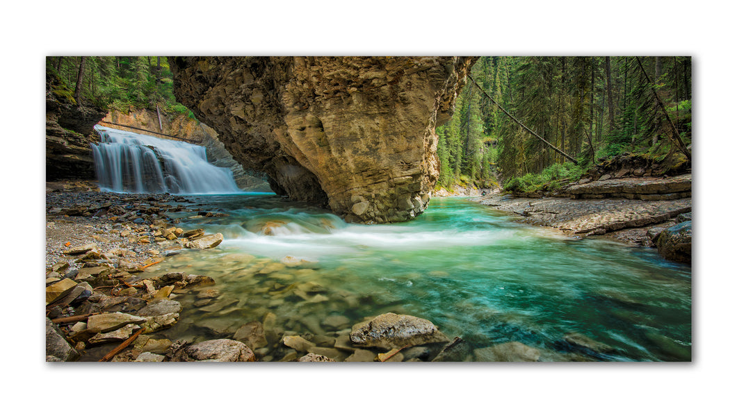 Once a hidden Gem in Johnston Canyon in the Banff National Park is now closed to foot traffic for environmental reasons. This amazing photo showcases the rock formations in the mountains and powerful waterfalls that carry the aqua water through the forest