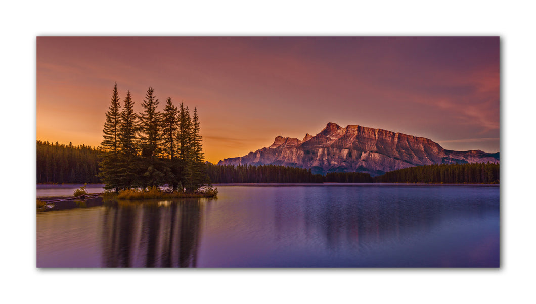 A spectacular sunrise at Two Jack Lake near Banff Alberta Canada. Enjoy as the warm rays from the sun flood the mountain peaks