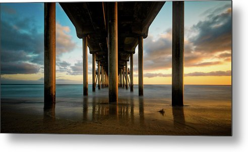 A popular California pier showcases the amazing california sunsets, you can almost see the transition from day to night with the vibrant golden colors contrasting with the cool light as day slips away