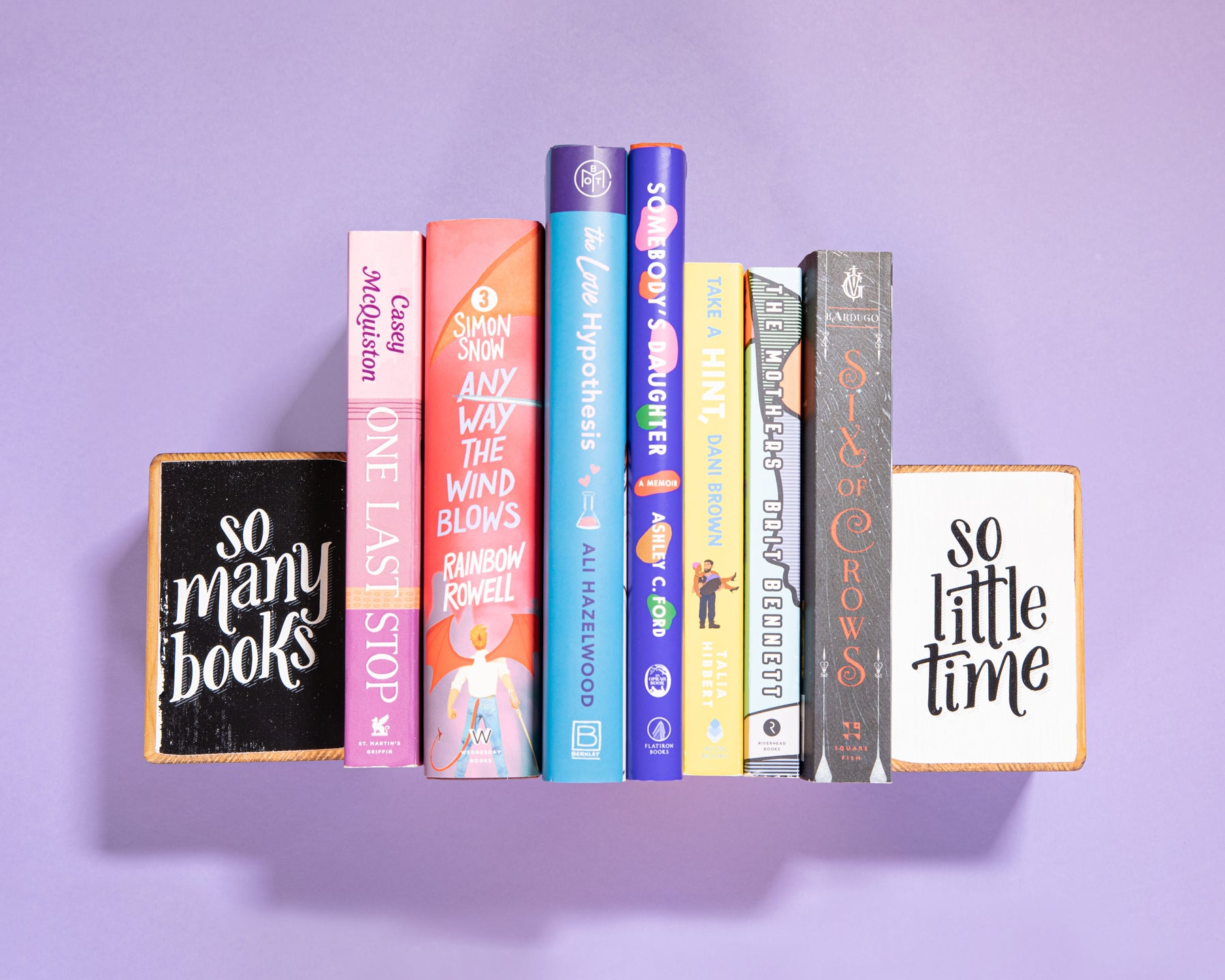 Group of 7 book recommendations to read by women authors, sandwiched between to wood bookends by ARCHd